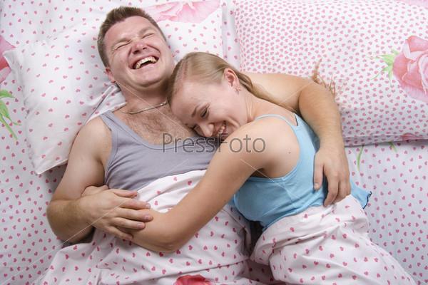 Фотография на тему Молодая пара лежат в постели и смеются