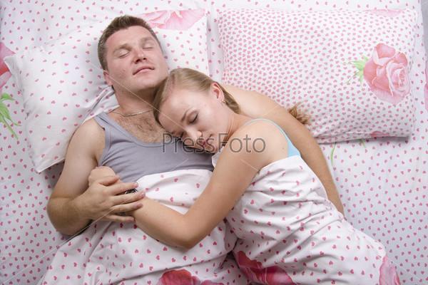Фотография на тему Молодая пара спит в постели