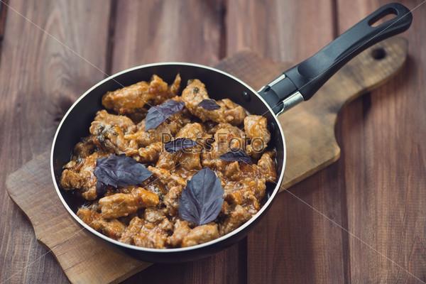 Жареная свинина в сковороде на деревянном фоне