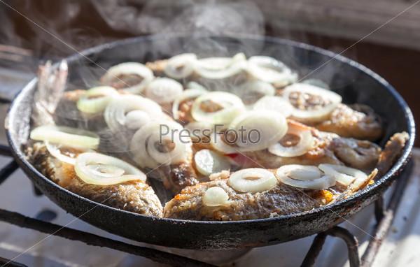 Жареная рыба в старой сковороде