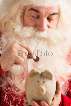 Фотография на тему Санта-Клаус кладет золотую монету в копилку