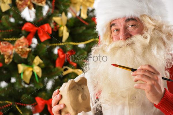 Санта-Клаус держит копилку и красит ее