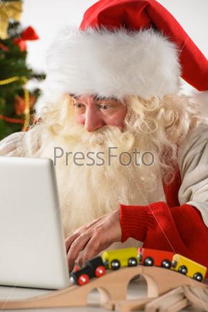 Фотография на тему Удивленный Санта Клаус работает на ноутбуке
