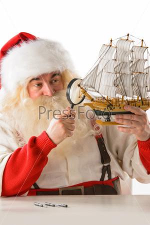 Санта-Клаус  делает новые игрушки в мастерской