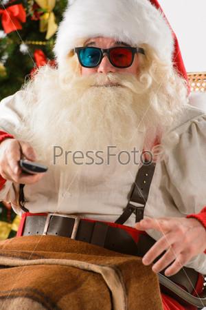 Санта-Клаус сидит в кресле-качалке возле елки дома и смотрит телевизор