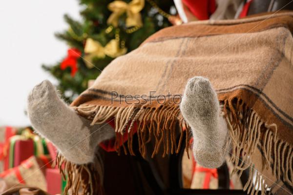 Санта-Клаус сидит в кресле-качалке возле елки и греет ноги
