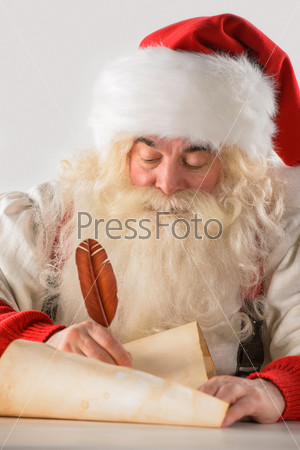Санта-Клаус пишет список подарков или отвечает на письма детей