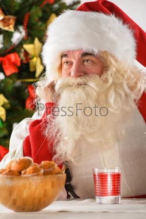 Фотография на тему Счастливый Санта-Клаус ест печенье с чаем дома