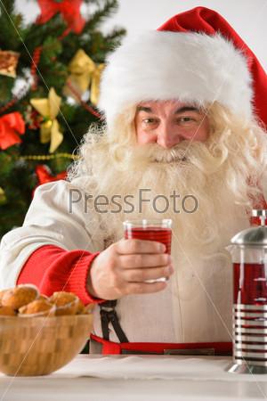 Счастливый Санта-Клаус ест печенье с чаем дома