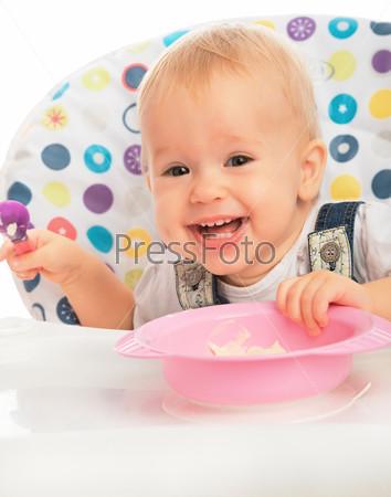 Счастливый малыш ест ложкой