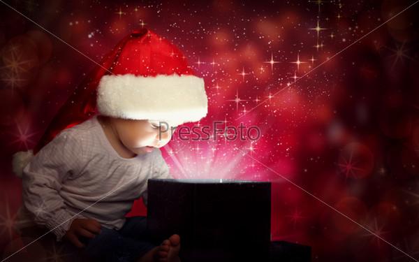 Фотография на тему Счастливый ребенок в Рождественском колпаке открывает волшебную шкатулку