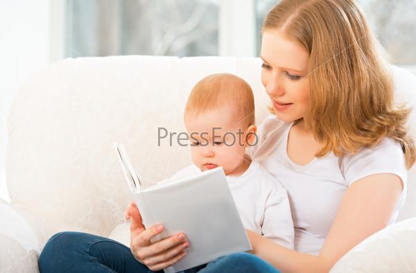 Фотография на тему Мать читает книгу маленькому ребенку на диване