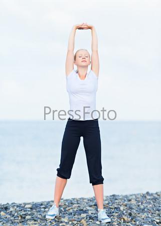 Женщина занимается йогой и спортом на пляже