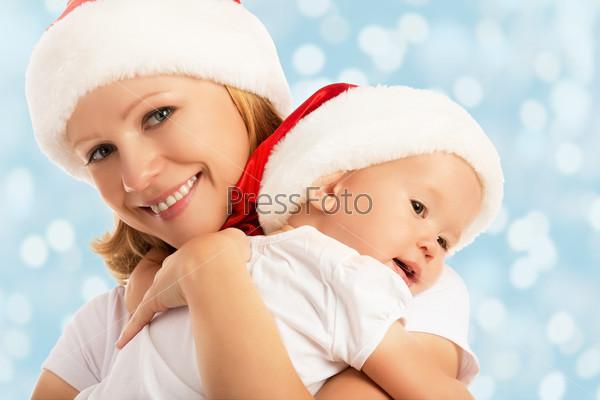 Счастливая мать и ребенок в Рождественских колпаках