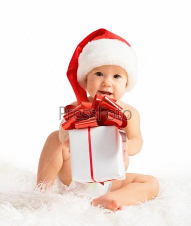 Счастливый малыш в Рождественском колпаке с подарком
