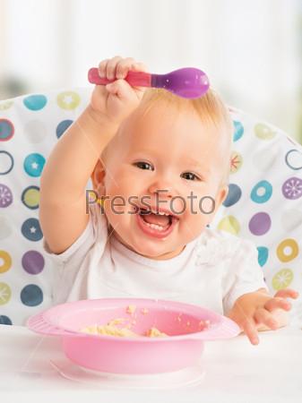 Счастливый ребенок ест сам ложкой