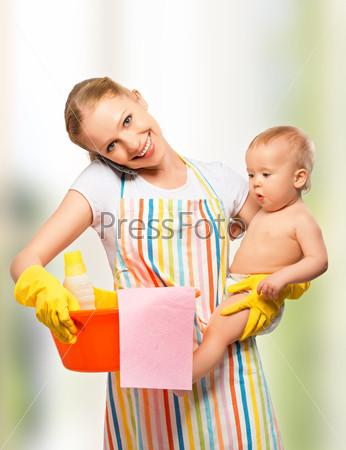 Молодая счастливая мать и домохозяйка с ребенком делает работу по дому и разговаривает по телефону