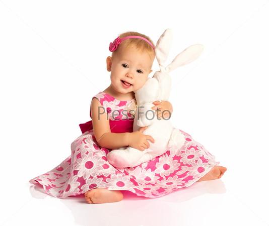 Девочка обнимает игрушечного кролика, изолированная на белом