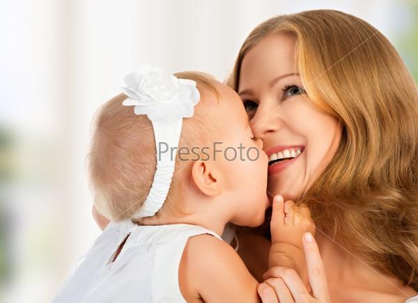 Счастливая мать целует ребенка