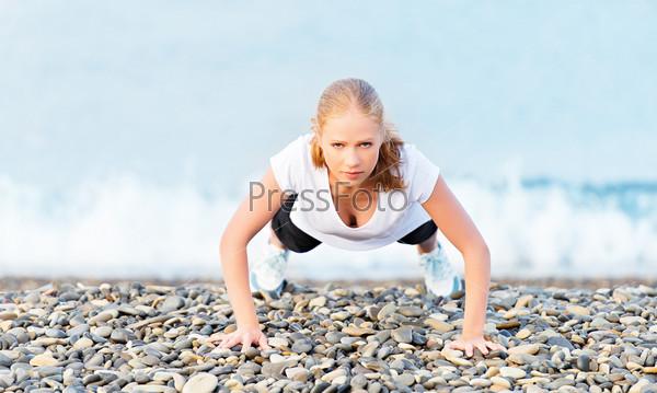 Фотография на тему Молодая здоровая женщина отжимается на открытом воздухе на пляже