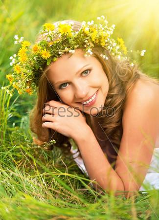 Красивая женщина в венке из цветов в зеленой траве на открытом воздухе