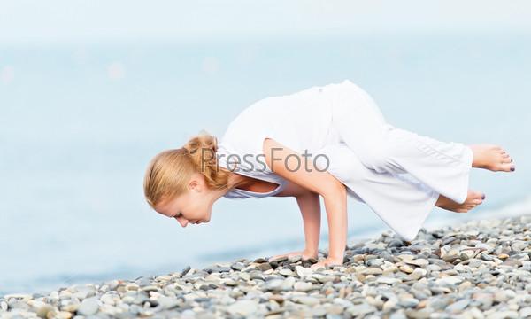 Женщина в белом занимается йогой на пляже
