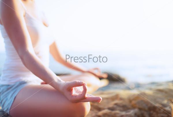 Руки медитирующей на пляже женщины