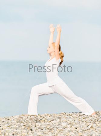 Фотография на тему Женщина в белом занимается йогой на пляже