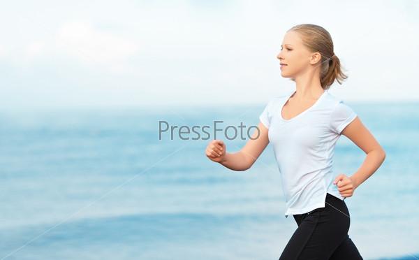 Фотография на тему Молодая женщина бежит на берегу моря