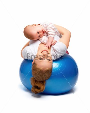 Мать и ребенок делают гимнастические упражнения на мяче