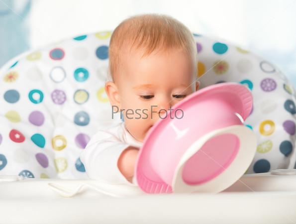 Ребенок ест из розовой тарелки