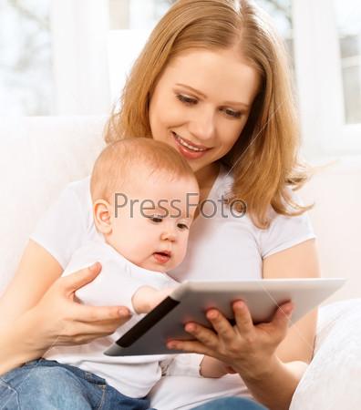 Мать и ребенок с планшетным компьютером на диване у себя дома