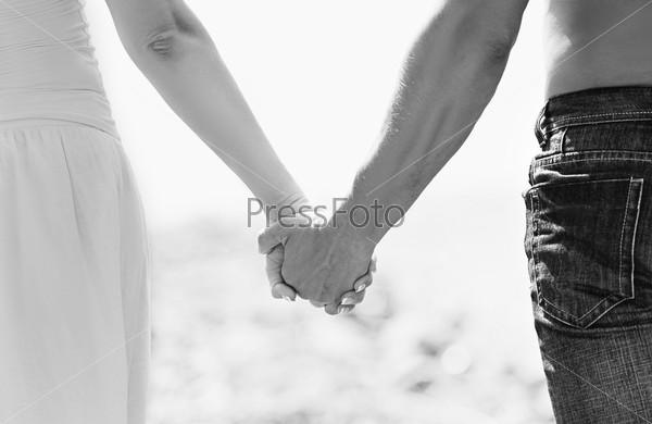 Концепция любви и семьи. Руки влюбленных, черно-белое фото