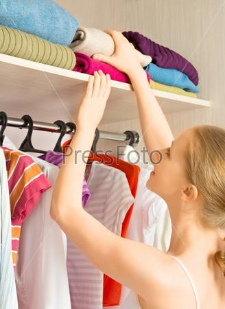 Фотография на тему Женщина выбирает одежду в домашнем гардеробе