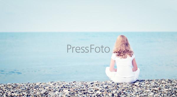 Одинокая молодая женщина сидит на пляже