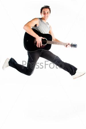 Молодой мужчина с гитарой в прыжке