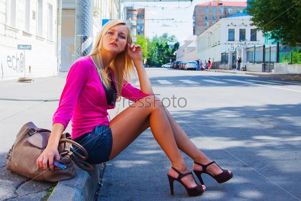 Фотография молодой и красивой девушки, гуляющей по улице