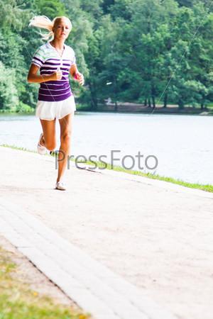 Молодая и красивая женщина бегает в парке