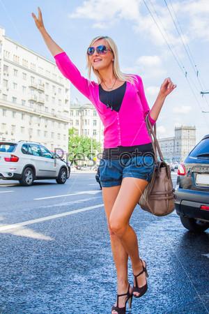 Красивая девушка пытается остановить такси