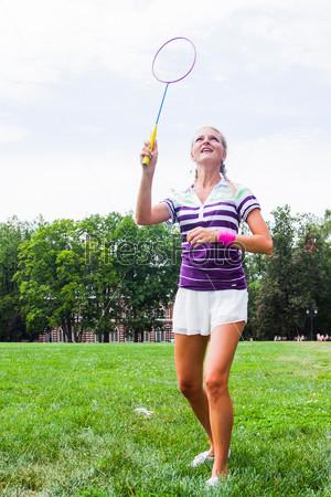 Красивая и молодая женщина играет в бадминтон