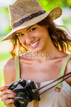 Счастливая девушка с фотоаппаратом на природе