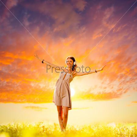 Девушка в наушниках на закате