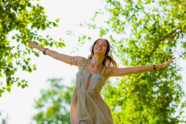 Счастливая девушка в наушниках на открытом воздухе