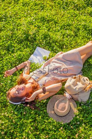 Женщина в наушниках лежит на траве
