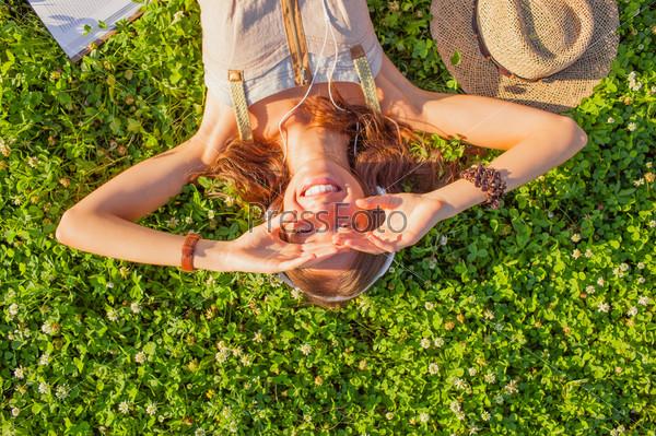 Фотография на тему Женщина в наушниках лежит на траве