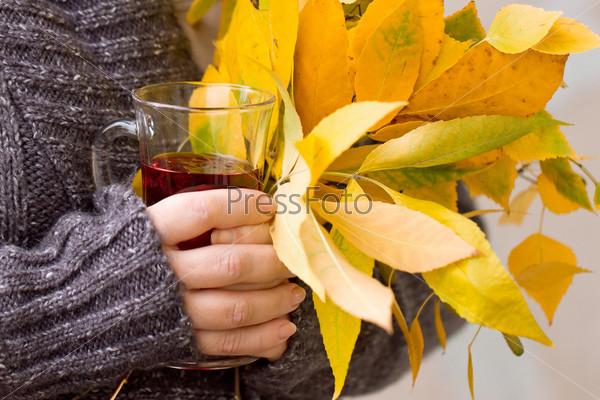 Женская рука держит чай и осенние листья