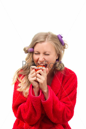 Девушка в красном халате ест помидор