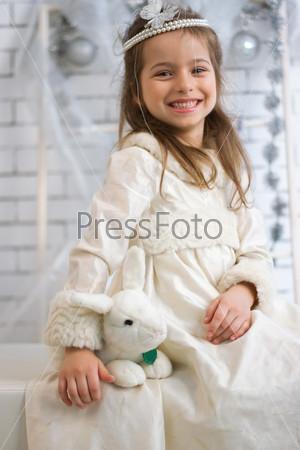 Девочка в праздничном платье с игрушечным кроликом