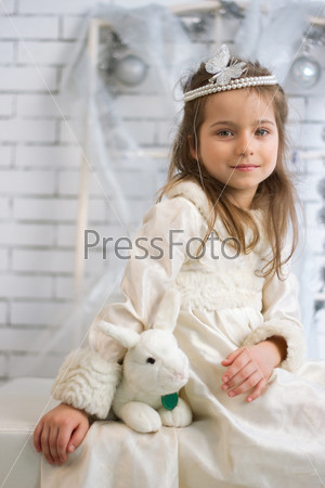 Девочка в зимнем праздничном платье с игрушечным кроликом