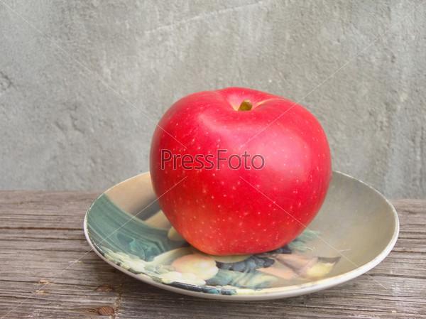 Красное яблоко на тарелке